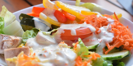 picture of salad with creamy salad dressing drizzled on top